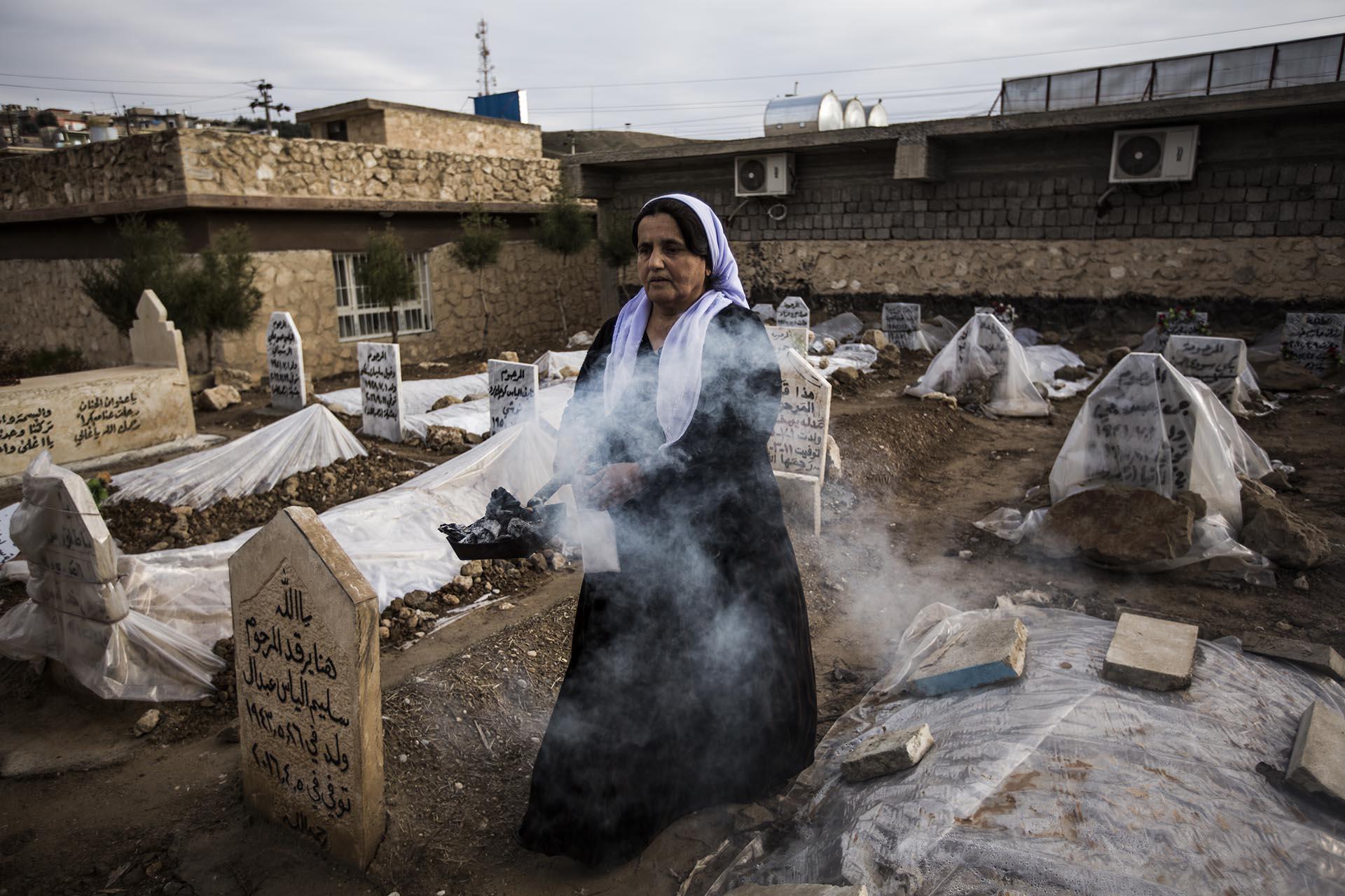 Una mujer purifica las tumbas de los yazidíes enterrados en el cementerio de Lalish durante la celebración del día de los muertos (Pablo Cobos)