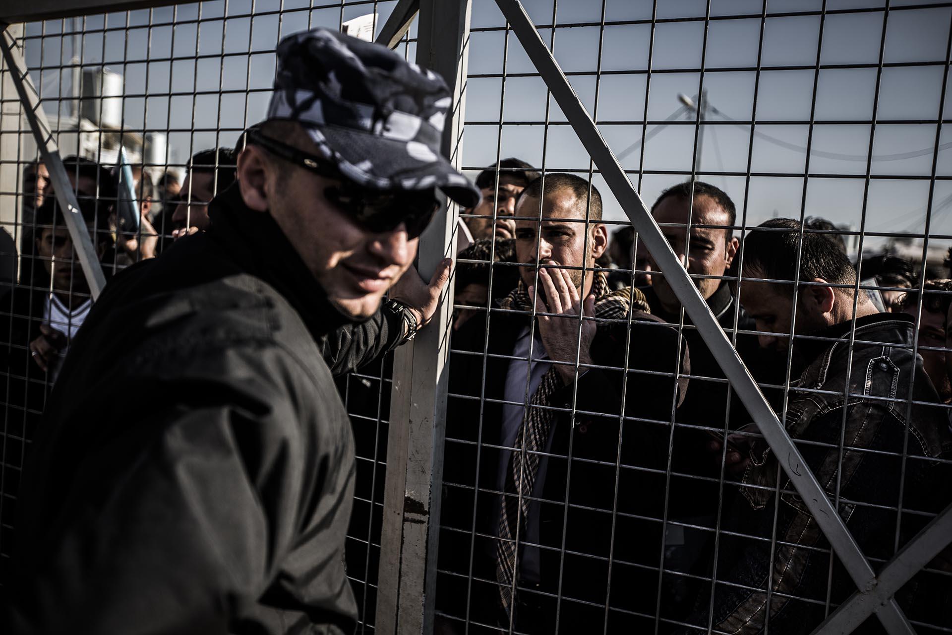 Cientos de hombres esperan cada día durante horas los permisos para acceder a un puesto de trabajo en el campo de refugiados (Pablo Cobos)