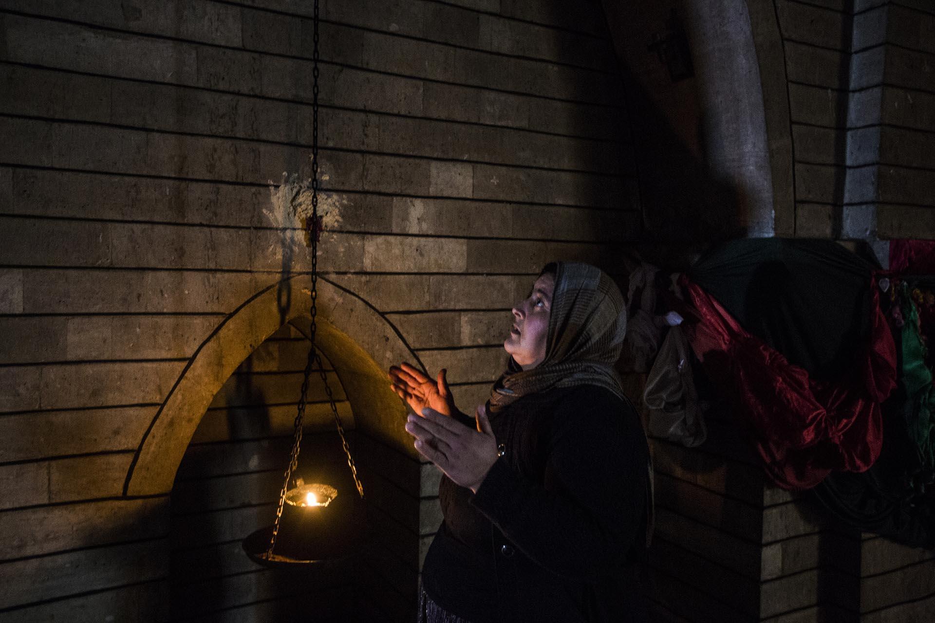 Una mujer reza en el interior del templo sagrado situado en las afueras de la ciudad de Lalish (Pablo Cobos)