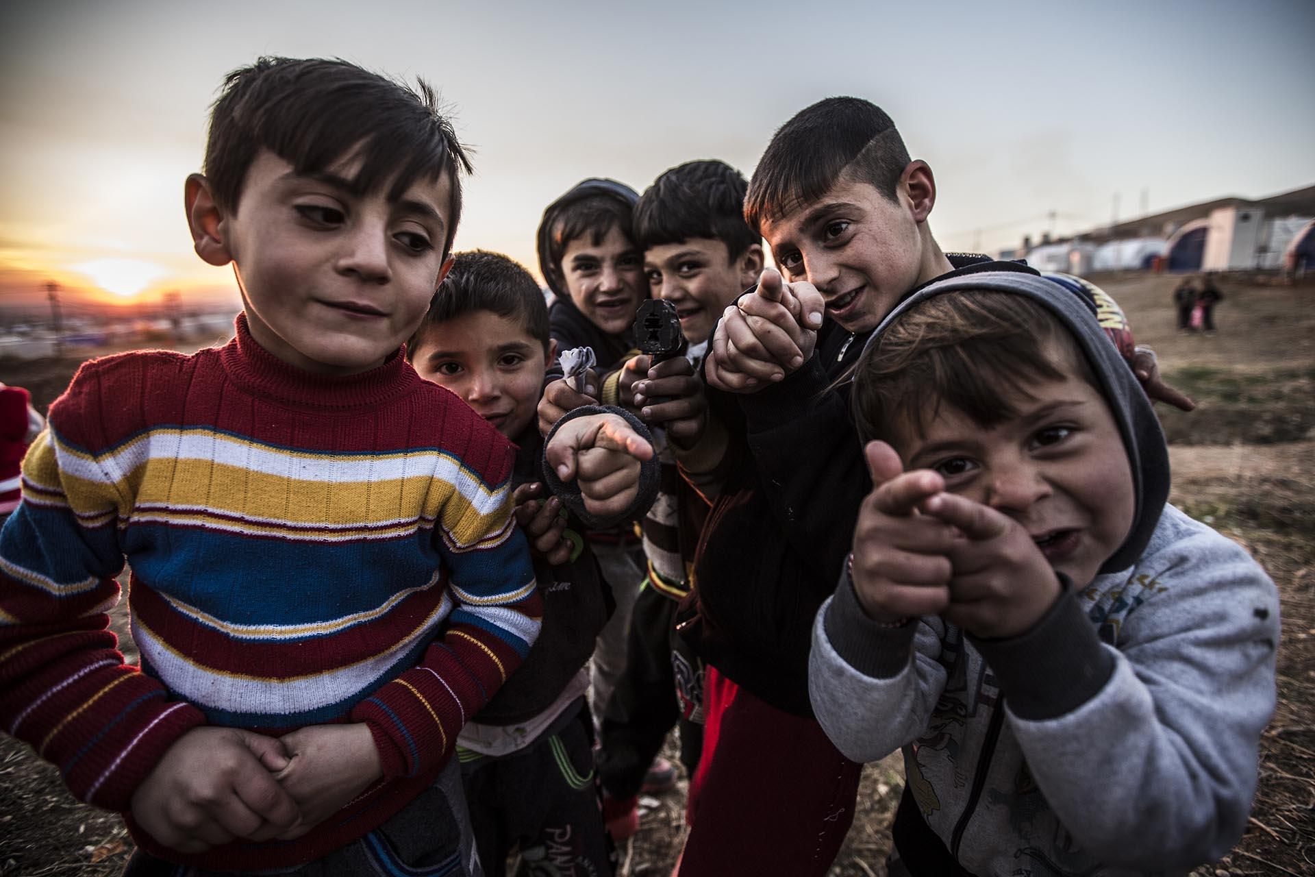 Un grupo de niños yazidíes juegan con pistolas simuladas en elcampo de refugiados de Essian (Pablo Cobos)