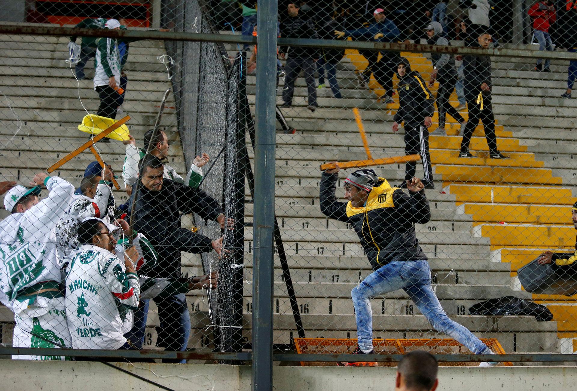 Hinchas de Palmeiras y Peñarol se enfrentaron en las tribunas tras la brutal pelea entre jugadores (Reuters)